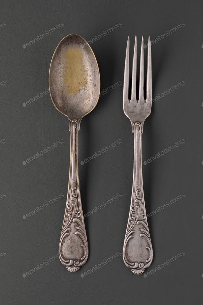 old scratched silver spoon and fork arranged in gray background