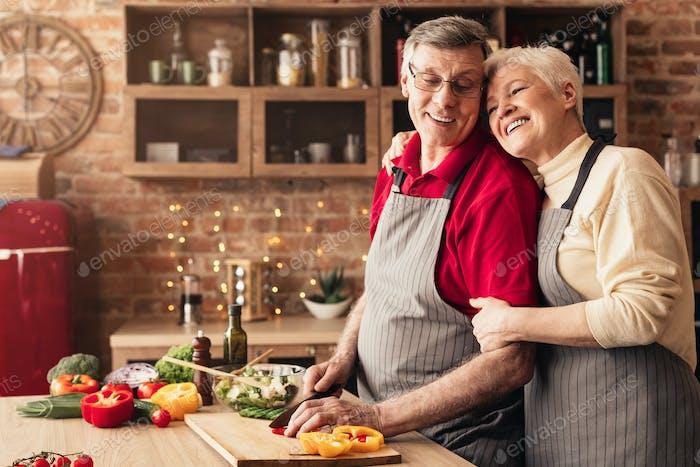 Senior woman embracing her cooking man at kitchen