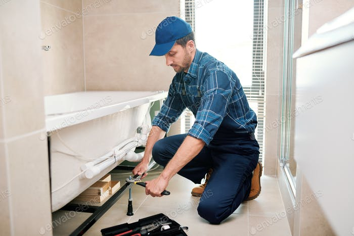 Young plumber or technician preparing detail for bathtub installation