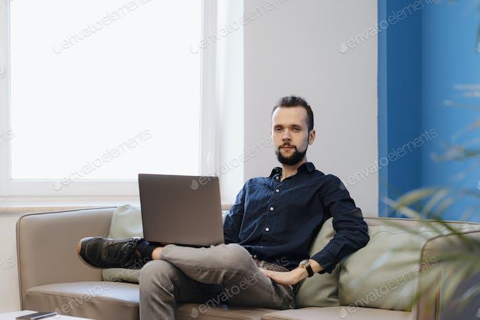 Junger Mann, der am Laptop arbeitet, während er auf dem Sofa im Büro sitzt