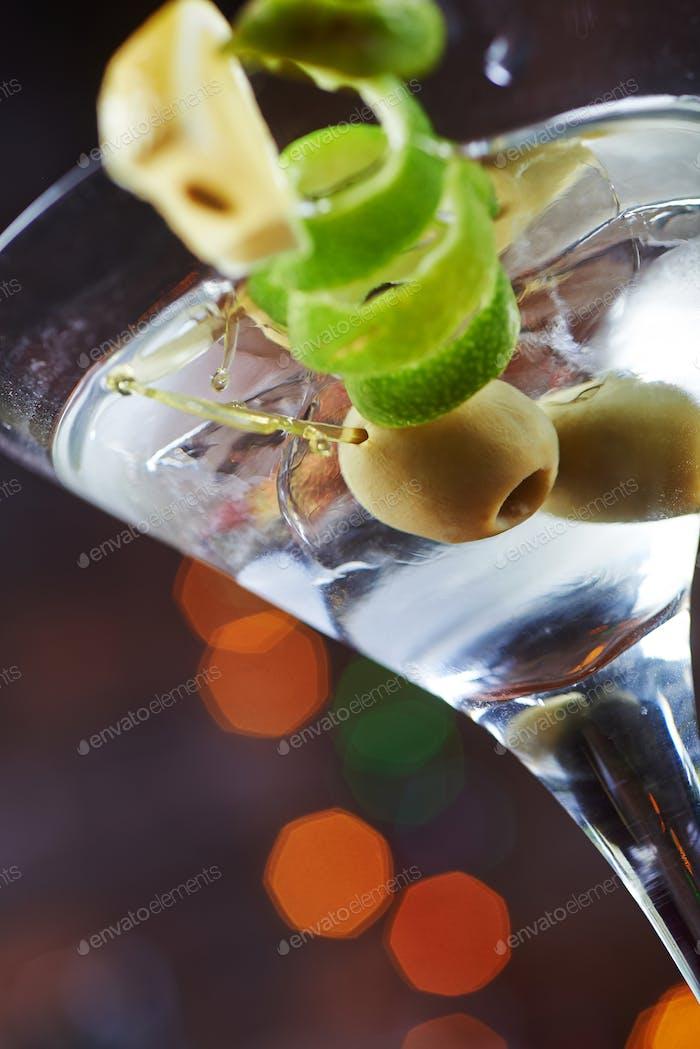 Glas kalter Martinis mit Oliven mit kreativer Dekoration Limette und Zitronen. soft focus.