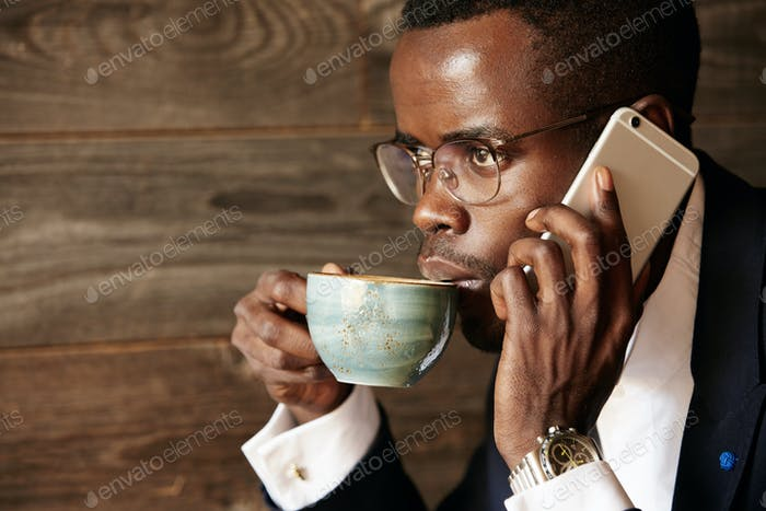 Young African businessman talking on mobile phone while working at the cafe. Young black corporate w
