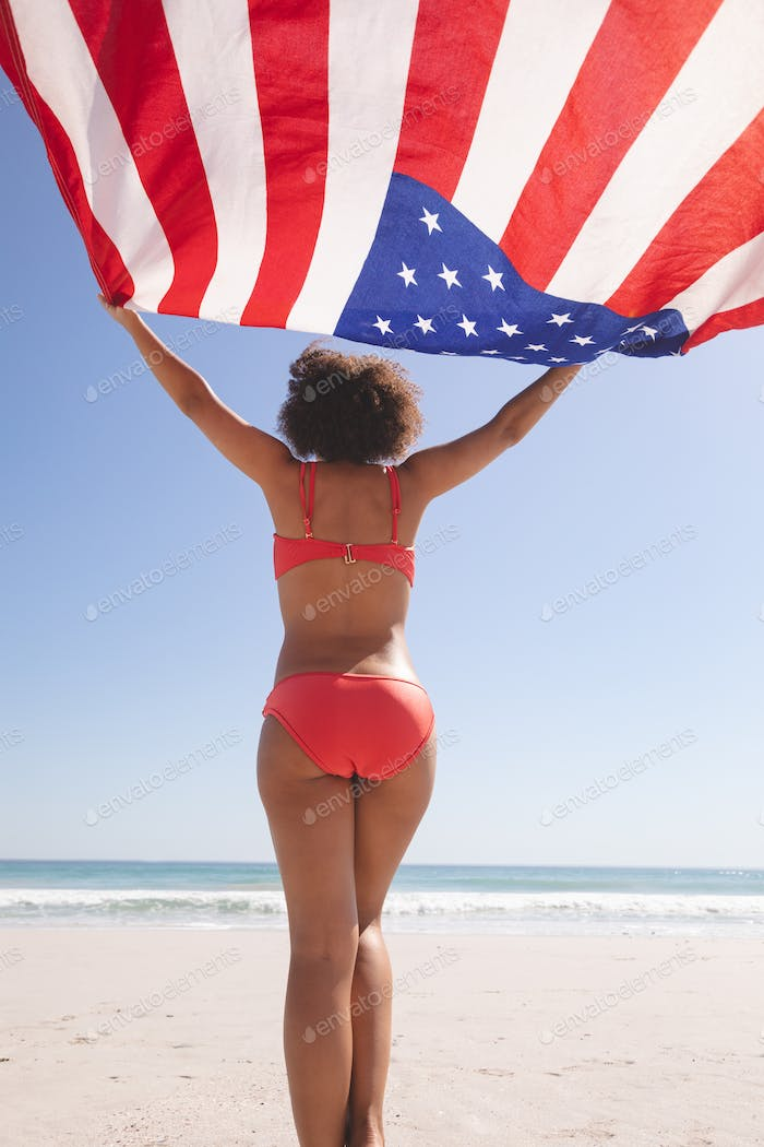 Rear view of African american woman in bikini holding american flag on the beach