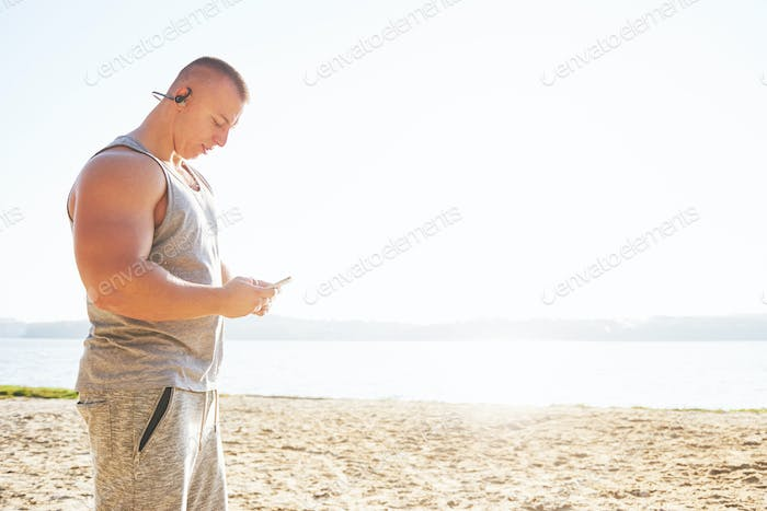 A athletic man looking at the seaside on the wild sand beach