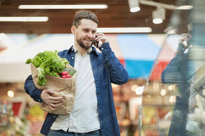 Bearded Man Calling by Smartphone in Supermarket