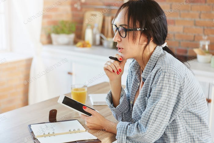 Beautiful female model with dark pony tail, dressed casually, uses modern digital tablet, counts cal