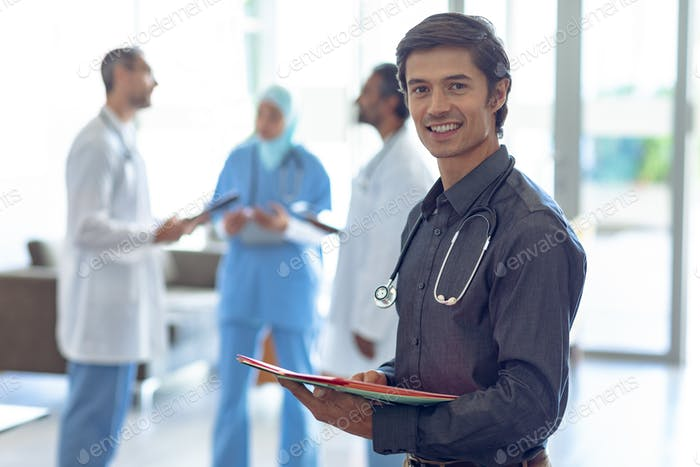 Caucasian male doctor holding medical file and looking at camera in hospital.