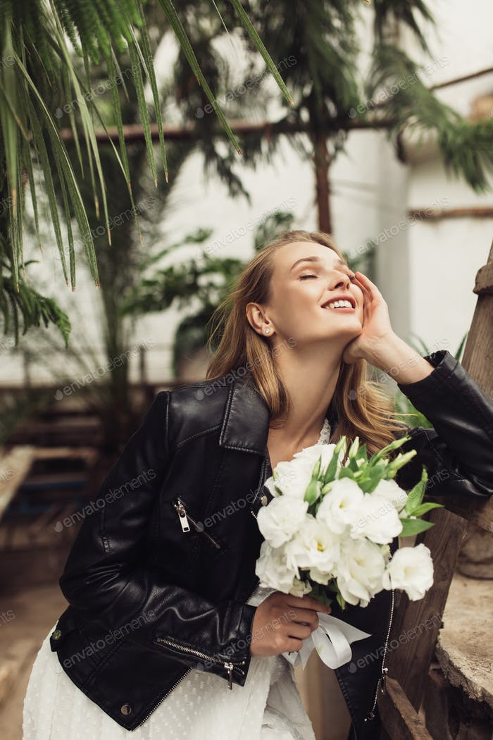 Young attractive smiling woman in black leather jacket and white