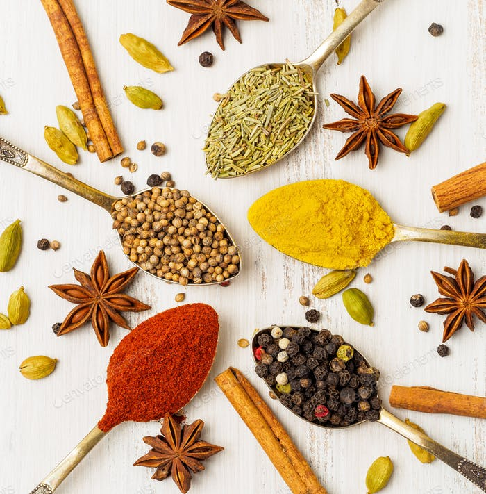 Mix of Indian spices in spoons on white wooden table, top view. Background with seasonings