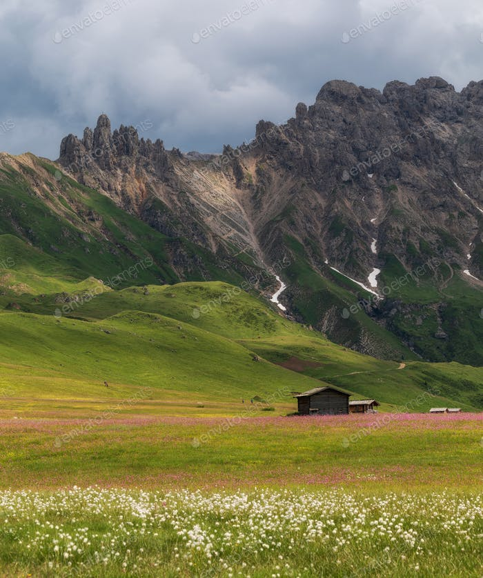 Cottages on the meadows in the Dolomites mountains