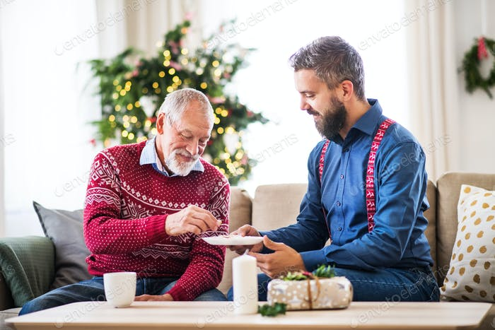 A senior father and adult son sitting on a sofa at Christmas time, eating biscuits.