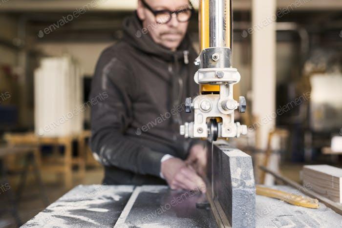 Tischler mit Bandsäge Holz in der Werkstatt schneiden