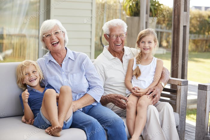 Grandparents With Grandchildren Relaxing On Deck At Home