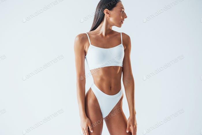 Beautiful woman with slim body in underwear is in the studio