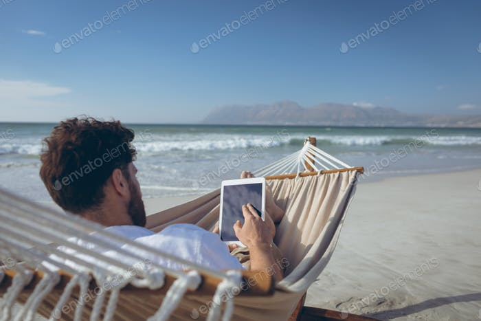 Rear view of young Caucasian man using digital tablet while lying on hammock at beach on sunny day