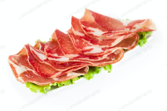 Thinly sliced ??ham on a white plate