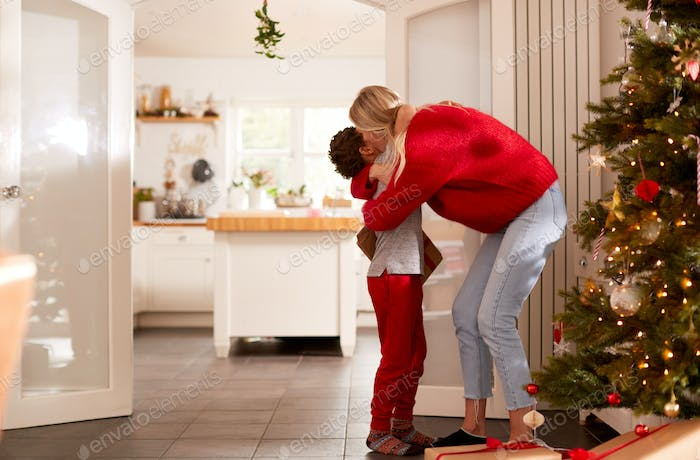Son Giving Mother Gift On Christmas Morning At Home