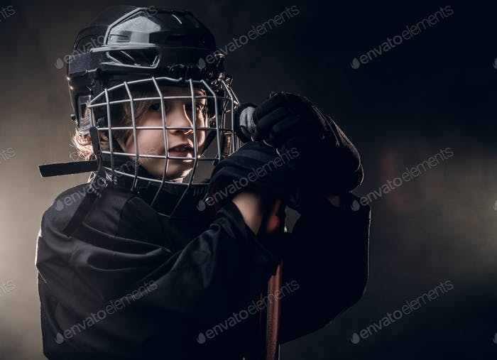 Young hockey player posing in uniform for a photoshoot in a studio