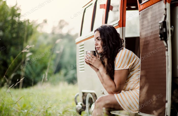A young girl sitting in a car on a roadtrip through countryside.