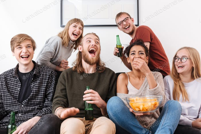 Happy laughing friends sitting on sofa and watching film together with chips and beer at home