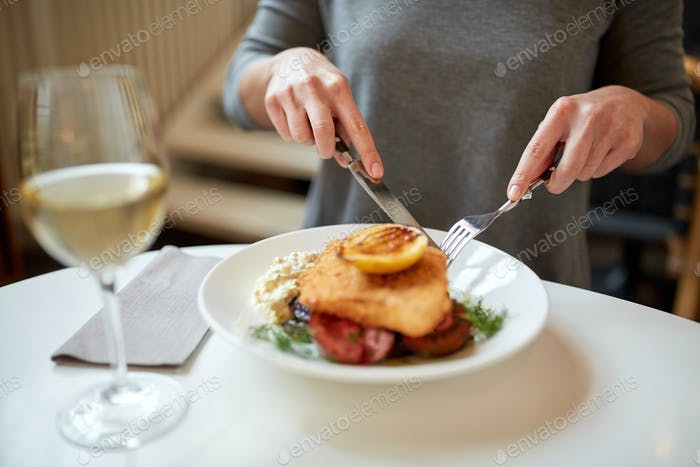 woman eating fish salad at cafe or restaurant