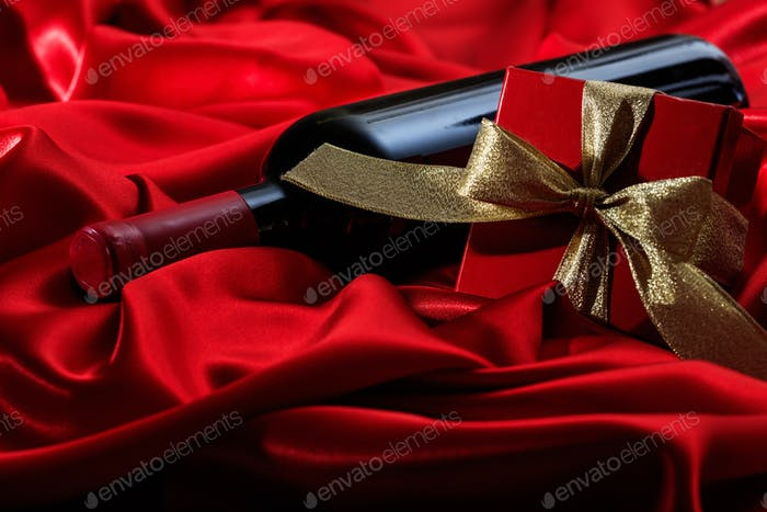 Valentines day. Red wine bottle and a gift on red satin