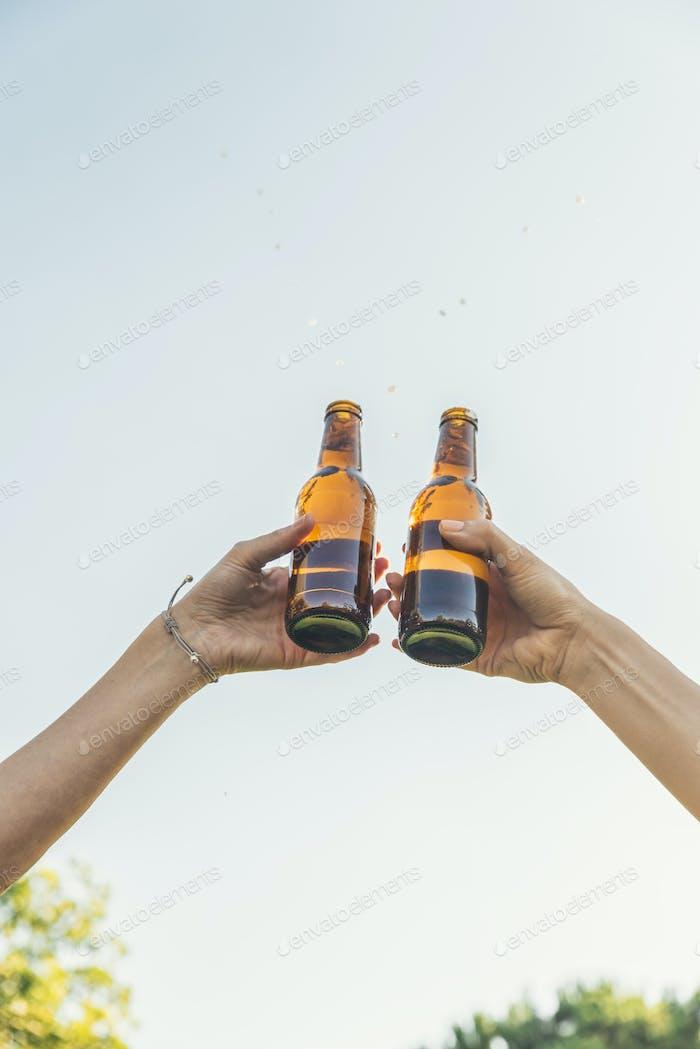 Weibliche Freunde jubeln klingeln Flaschen Bier.