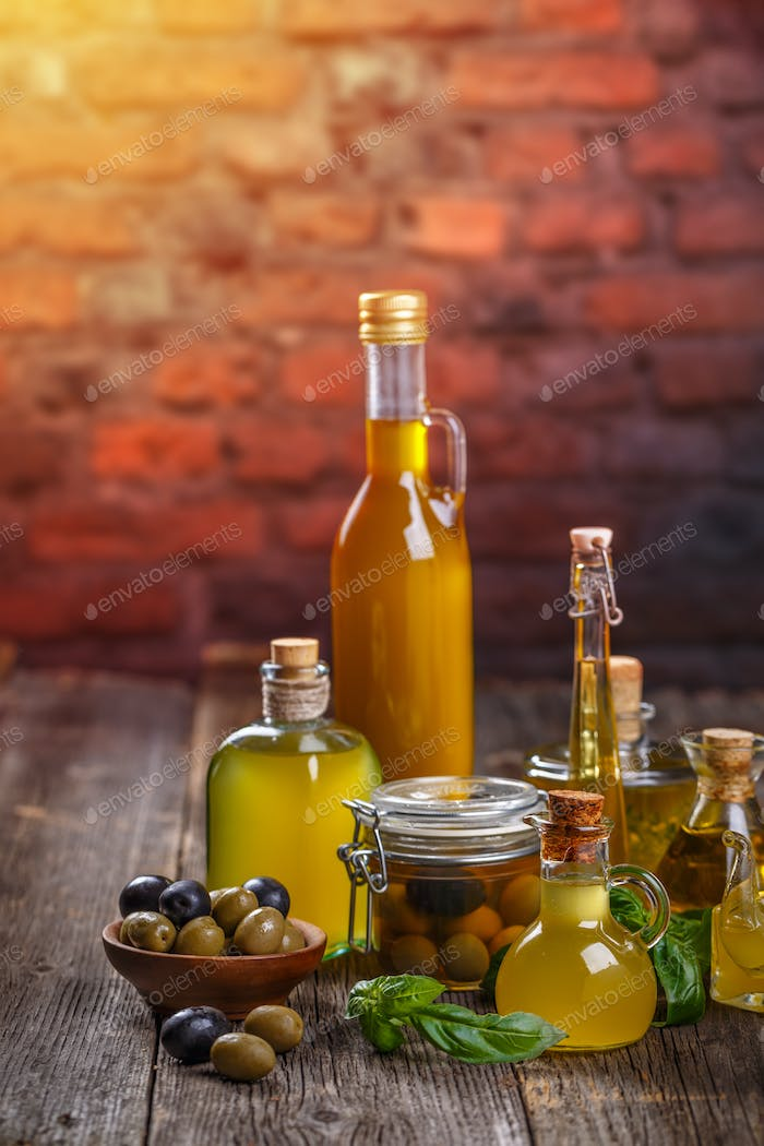 Olive oil in glass bottles and olives