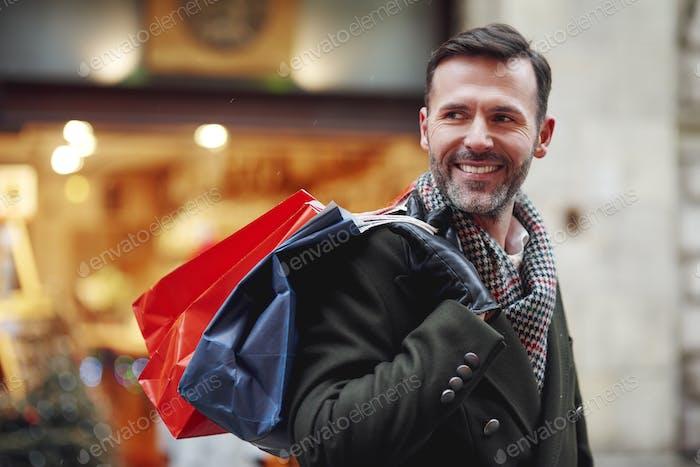 Hombre sonriente con bolsas de compras