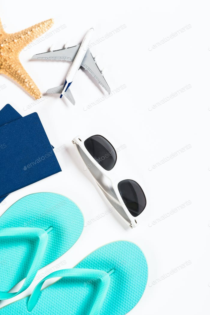Blue flip flops, sunglasses, passport, plane and starfish on white background