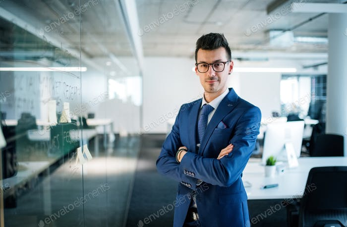 A portrait of young businessman standing in an office, arms crossed