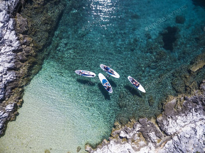 High angle shot of four people lying on paddleboards in a cove.