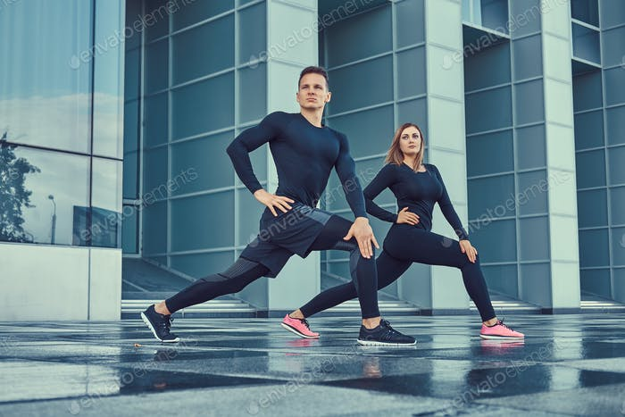 Young fitness couple in a sportswear, doing a workout outdoors near a skyscraper.
