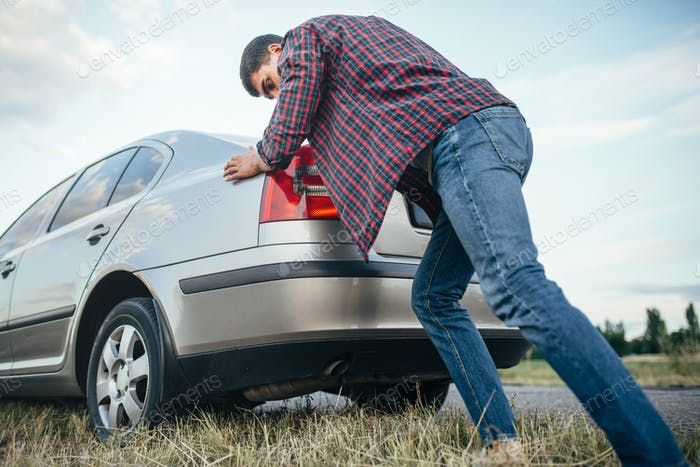 Man pushing broken car, side view