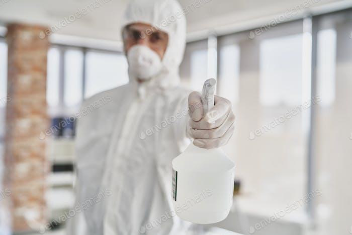 Mann hält Spray Desinfektionsmittel vor der Kamera