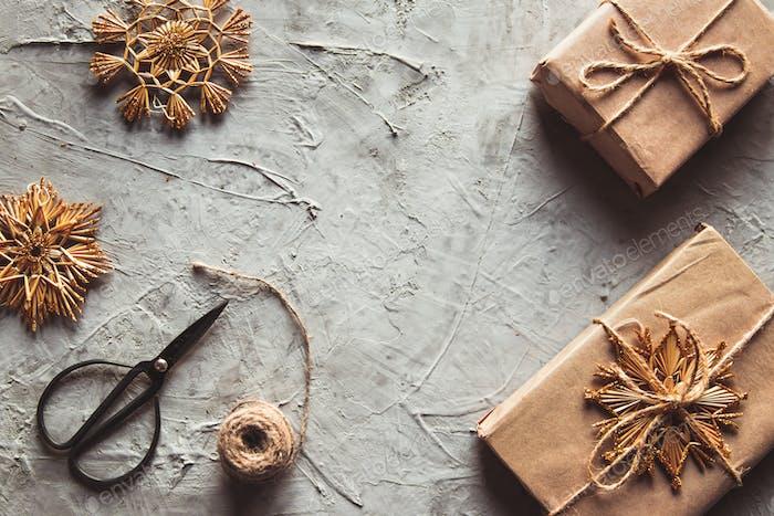 Weihnachtshintergrund Geschenke gewickeltes Papier, natürliche Dekorationen, Fichtenkegel