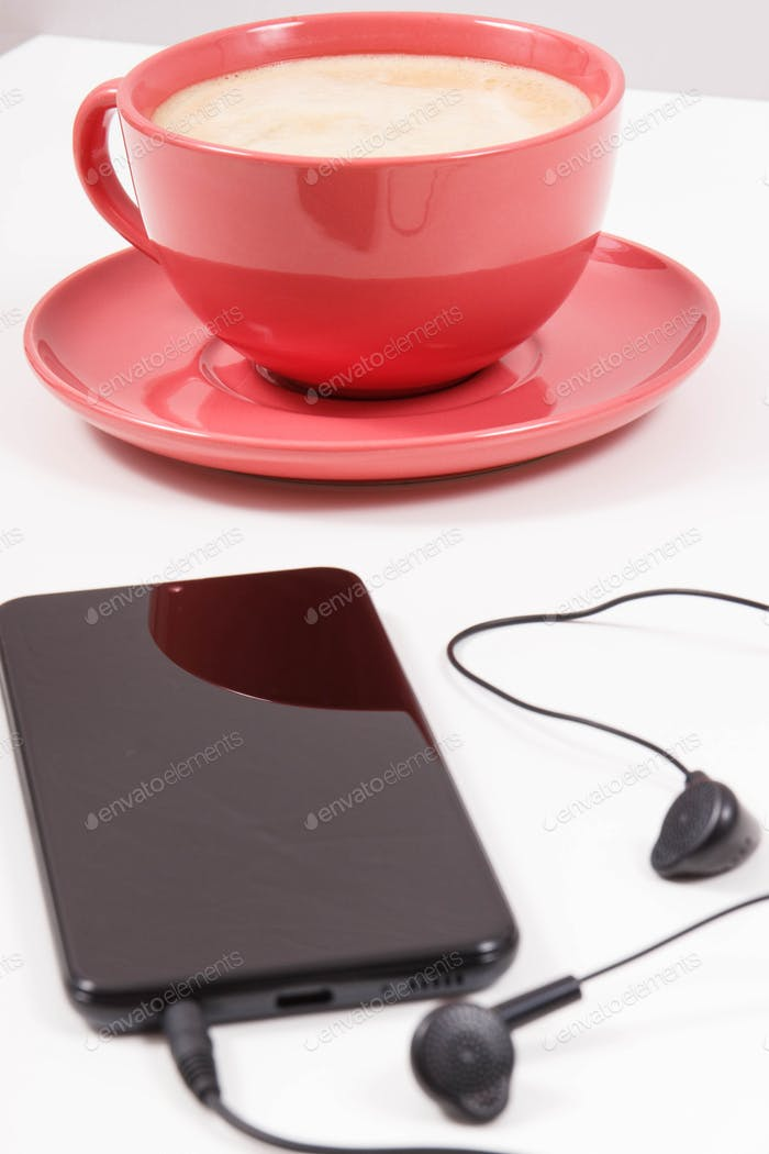 Smartphone with connected headphones and coffee with milk. Relaxation time with music