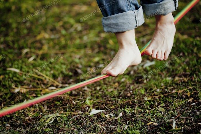 Niedriger Teil des Menschen zu Fuß auf dem Drahtseil über Gras im Park