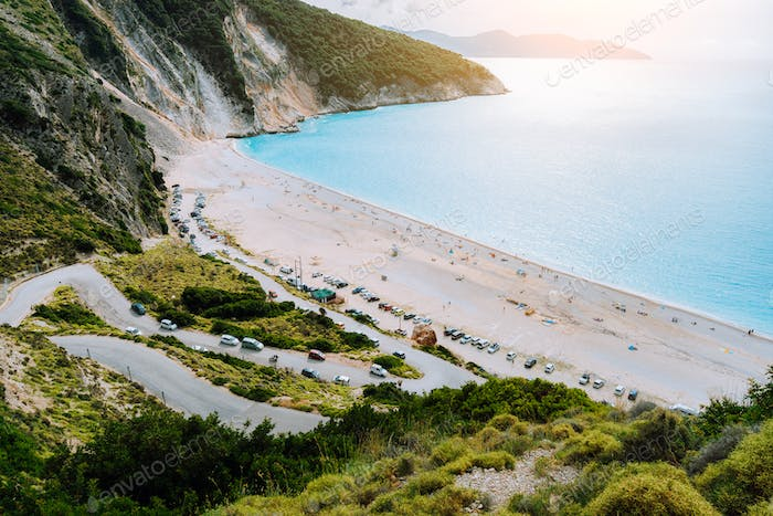View of serpentine road lead to Famous Myrtos Beach, Kefalonia, Greece. Visiting amazing blue bay