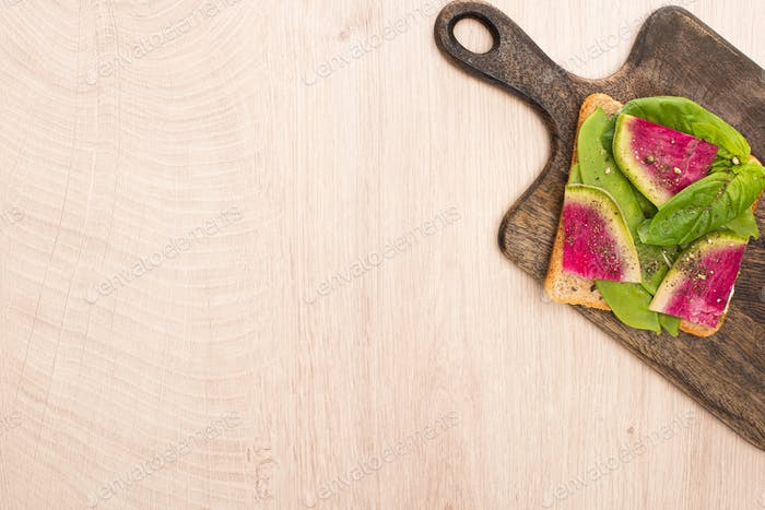 top view of vegetarian radish sandwich on wooden cutting board
