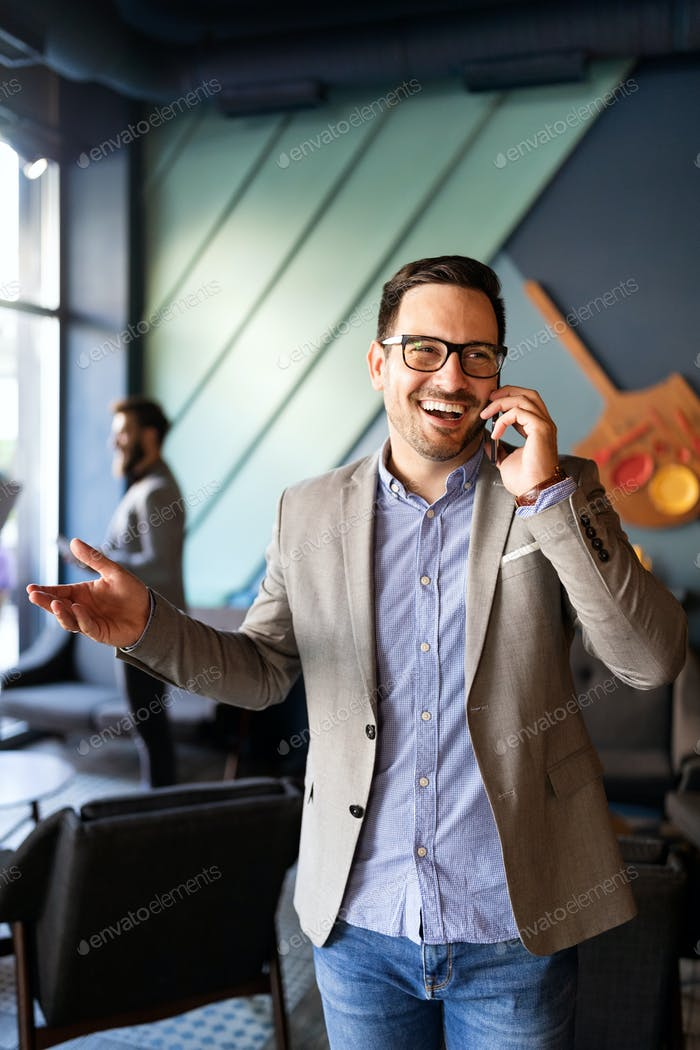 Business, people and office concept. Happy young businessman talking on phone in office