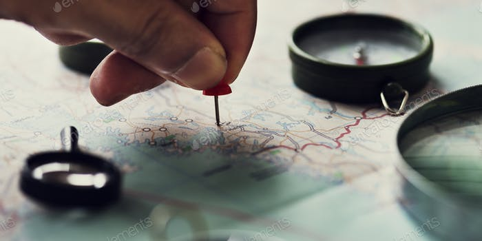 Closeup of hand pinning on world map journey travel