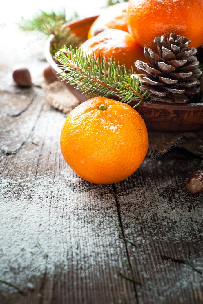 Tangerines, fir tree, pinecones and nuts. Christmas food decorations