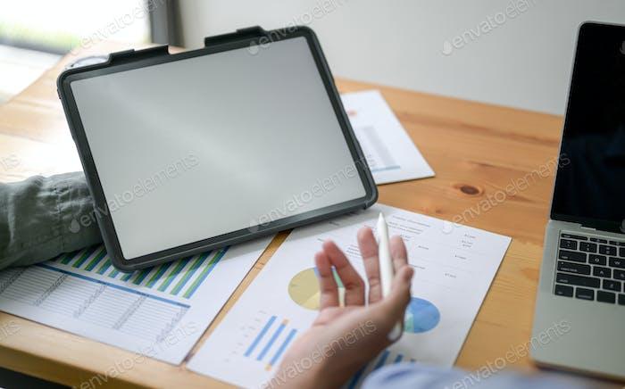 Abgeschnittene Aufnahme von Mitarbeitern präsentiert mit Tablet im Büro.