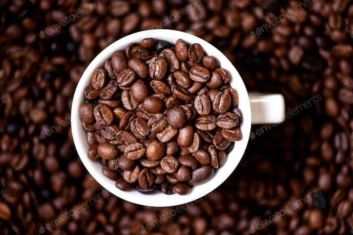 Coffee mug filled with coffee beans and coffee background