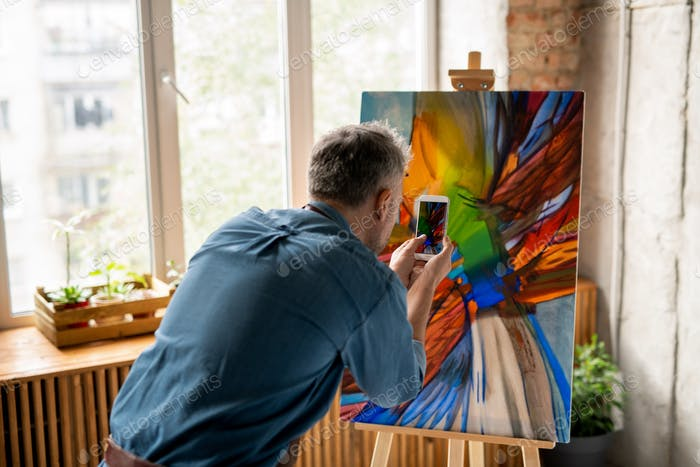 Contemporary man with smartphone taking photograph of the painting on easel