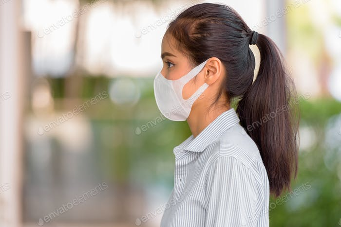 Profile view of woman wearing face mask to protect from coronavirus Covid-19