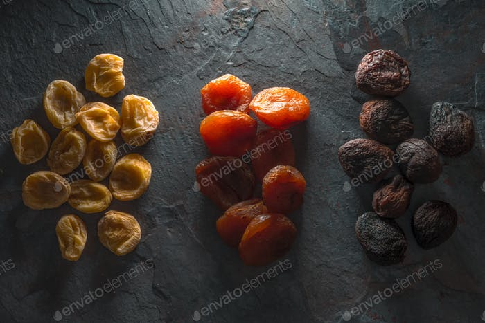 Groups of colorful dried apricots on a gray stone