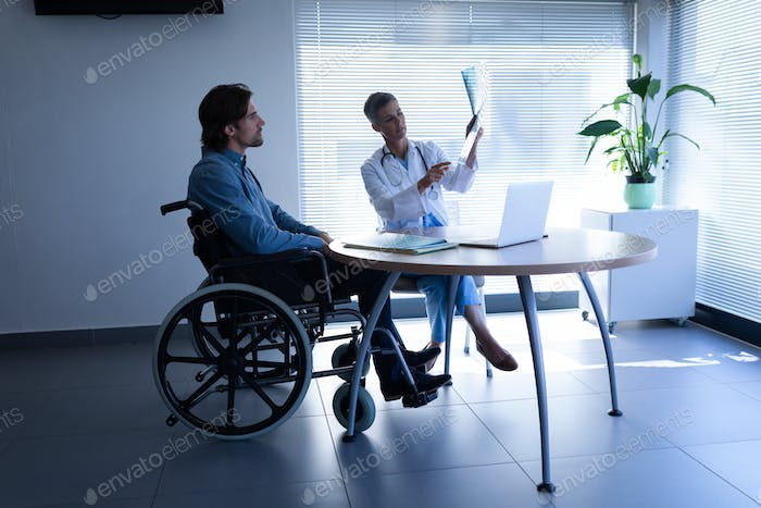 MMale doctor and disabled patient discussing over x-ray in clinic at hospital