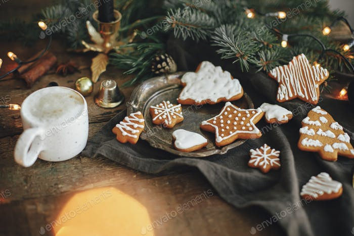 Winter hygge. Christmas gingerbread cookies, coffee, fir branches, warm lights on rustic table
